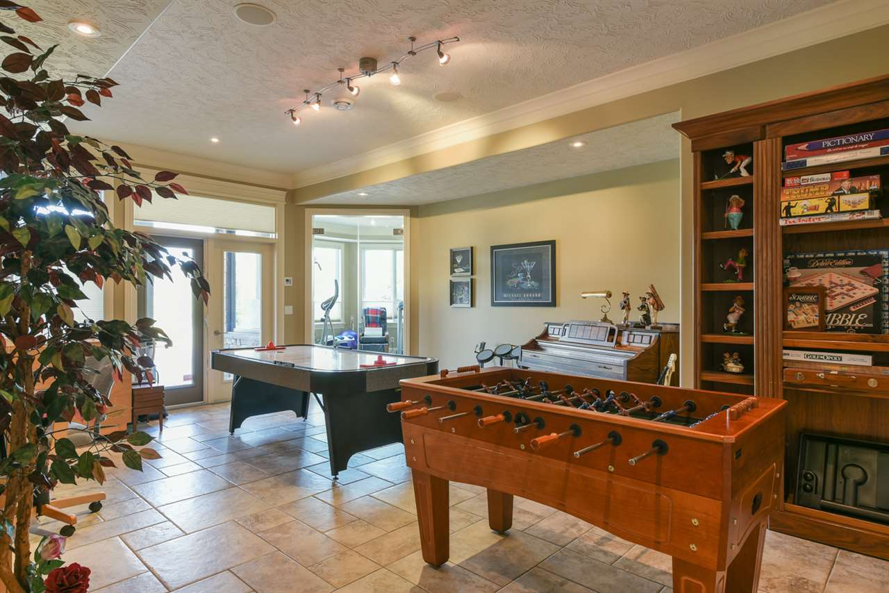 With lots of room for a pool table, ping pong table, board games or a card table, this generous games room has plenty of built in cabinets, counters and double doors that lead out to a patio.