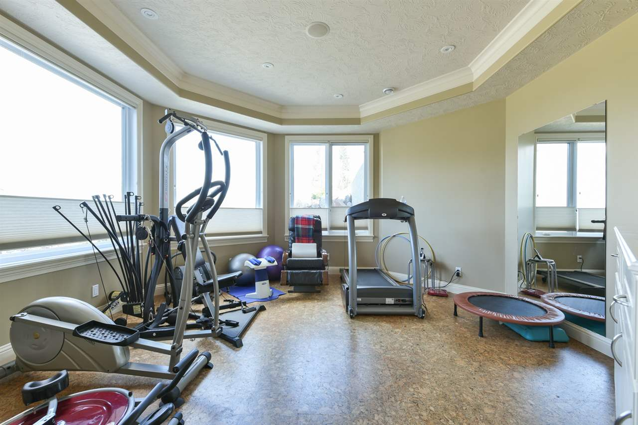 Windows and mirrors highlight this great exercise room with cork flooring and a double glass entrance!