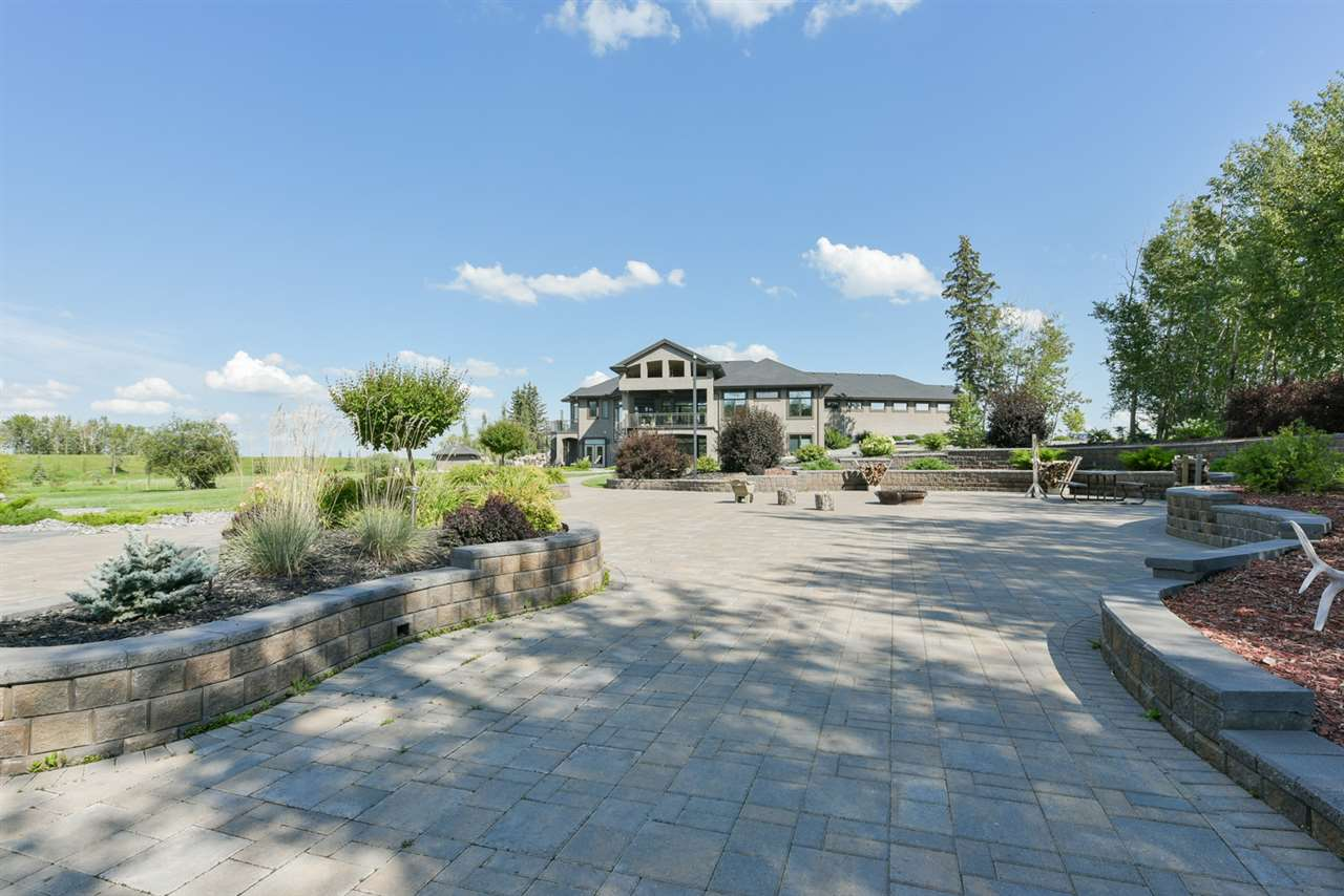 Covered patios, heated decks, fire pits, covered hot tub, circular staircases, gorgeous stone patios surrounded by perennial beds, aerated pond, irrigation system, miles of concrete and asphalt, a berm and many natural and planted trees!