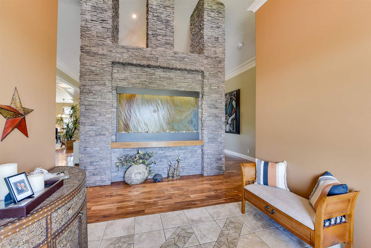 Rich crown moulding and overhead lighting in the generous foyer with gorgeous slate water wall and walk in closet & custom front door.