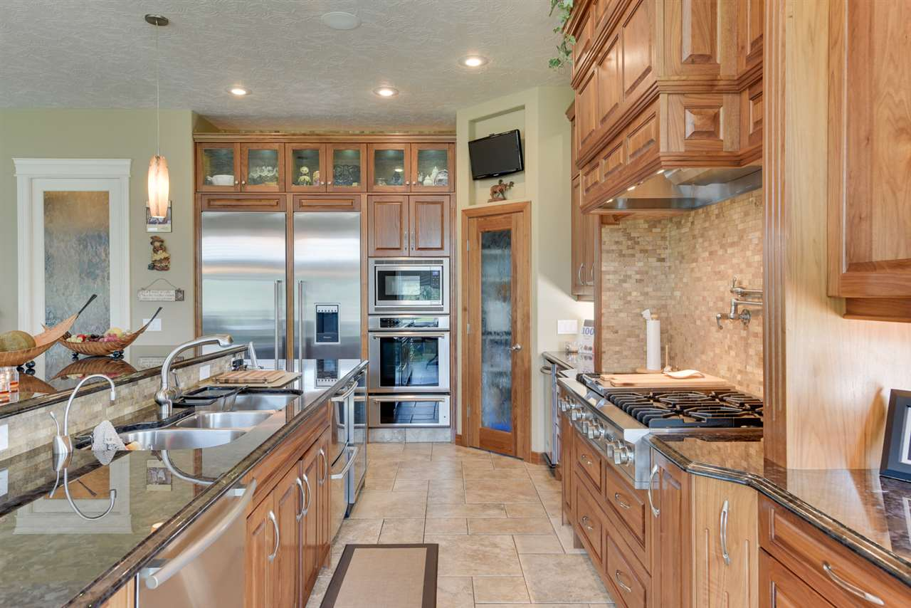 Rich stainless appliances, black walnut cabinets with all the extras, an appliance pantry, triple sink, custom lighting in the glass upper cabinets and a porcelain mosaic feature wall are just a few exceptional highlights.