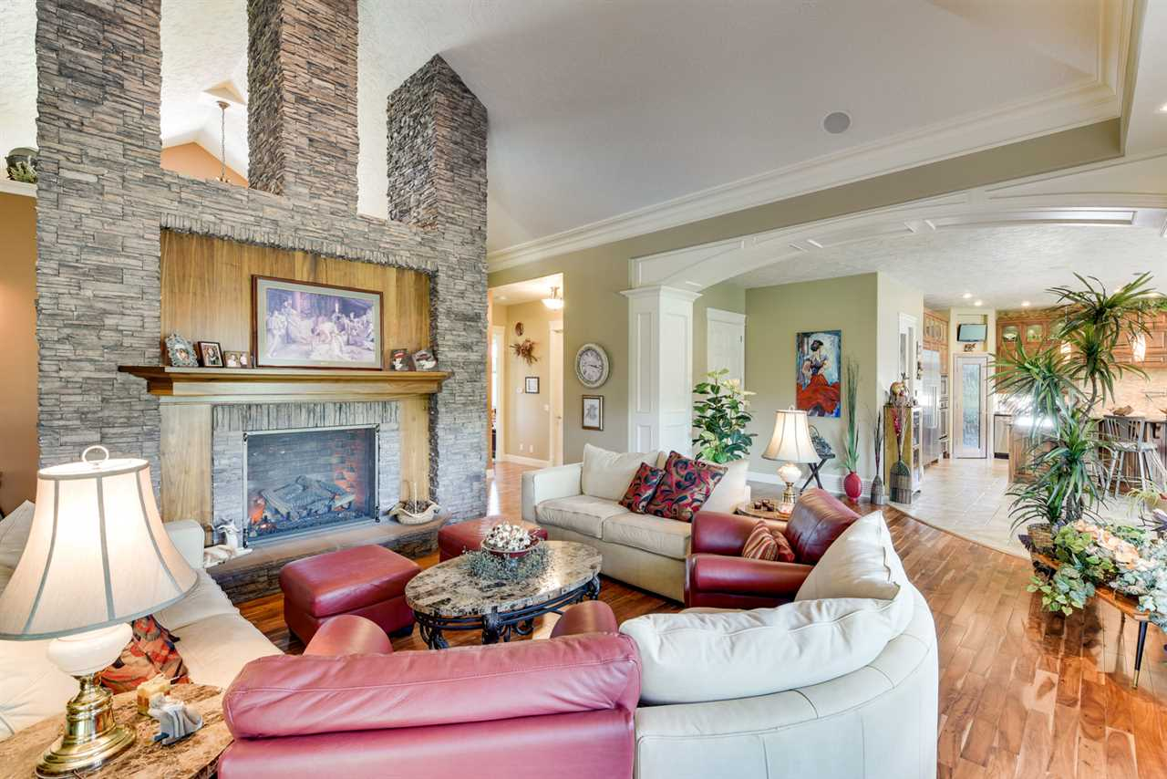 The stone fireplace and black walnut accents dominates this lovely Great Room. Custom blinds, vaulted ceilings with crown moulding, pot lighting and oversize windows plus the elevator access is located just off this fabulous central room.