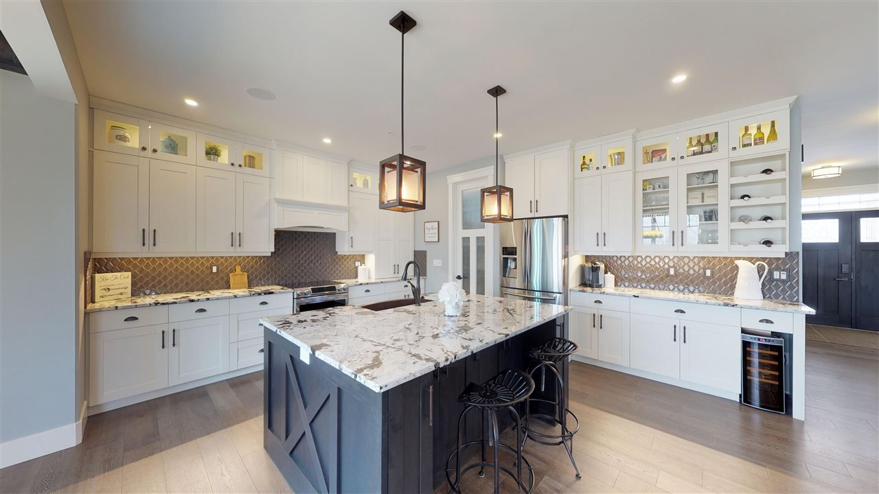 The well-appointed kitchen boasts exotic Brazilian granite counter tops, a huge island, plenty of classic white cabinetry with glass accents, under-cabinet lighting, high end appliances...too many features to list!