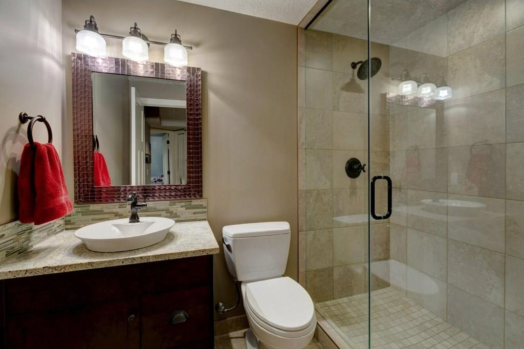 Basement 3 pc bath. Glass shower features extensive tile work and rainfall shower head. Cabinet has granite countertops and new sink. Bathroom is complete with heated tile flooring.