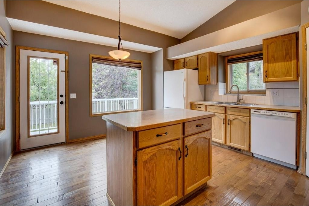 Loads of natural light flow into this bright and airy kitchen with vaulted ceilings and hardwood flooring. Kitchen island is moveable.