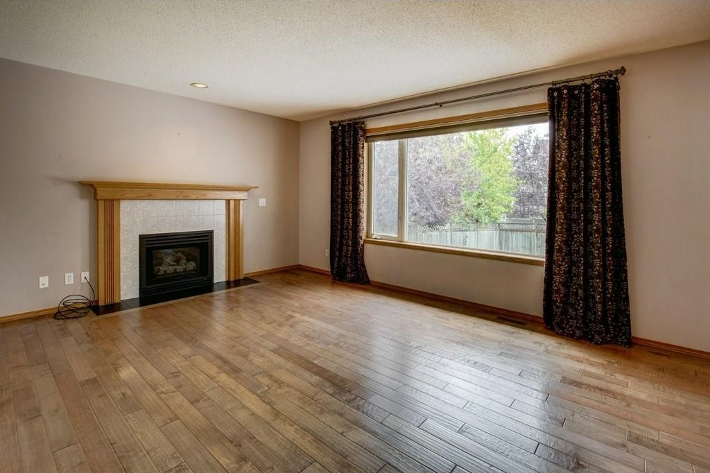 Spacious family/media room centered around the tiled gas fireplace. Bright room with south facing windows, custom curtains and blinds with hardwood flooring throughout.