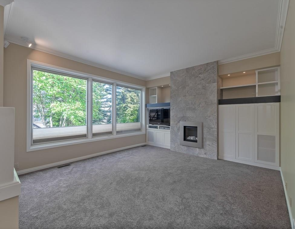 Spacious sunken family room with huge picture windows allowing for tons of natural light accented by tile trimmed fireplace and custom built-ins.