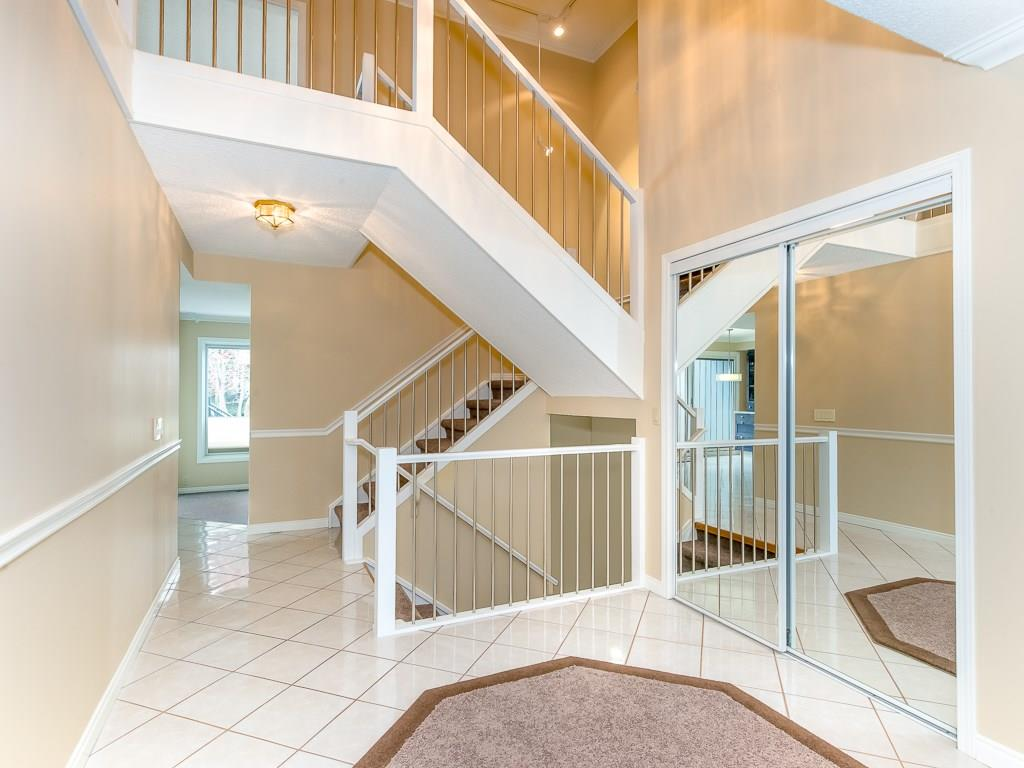 Grand foyer with two story cathedral ceilings, tile floors, closet with sliding glass doors and two piece powder bathroom.