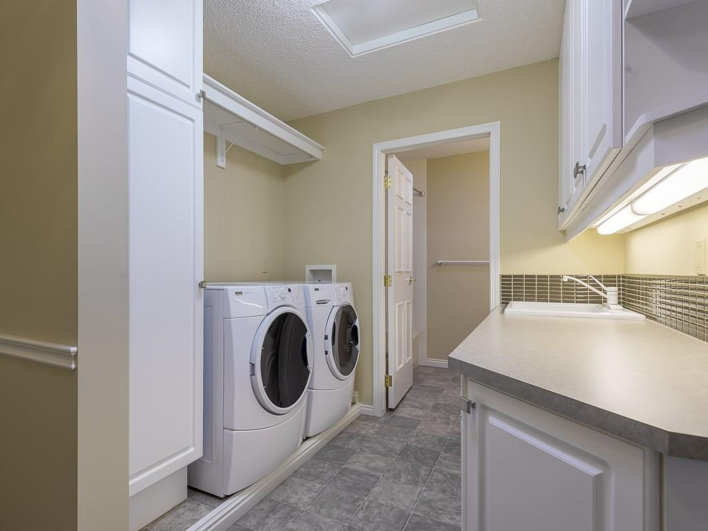 Laundry is conveniently located on the upper level having built-in cabinets and sink leading to main bathroom beyond.