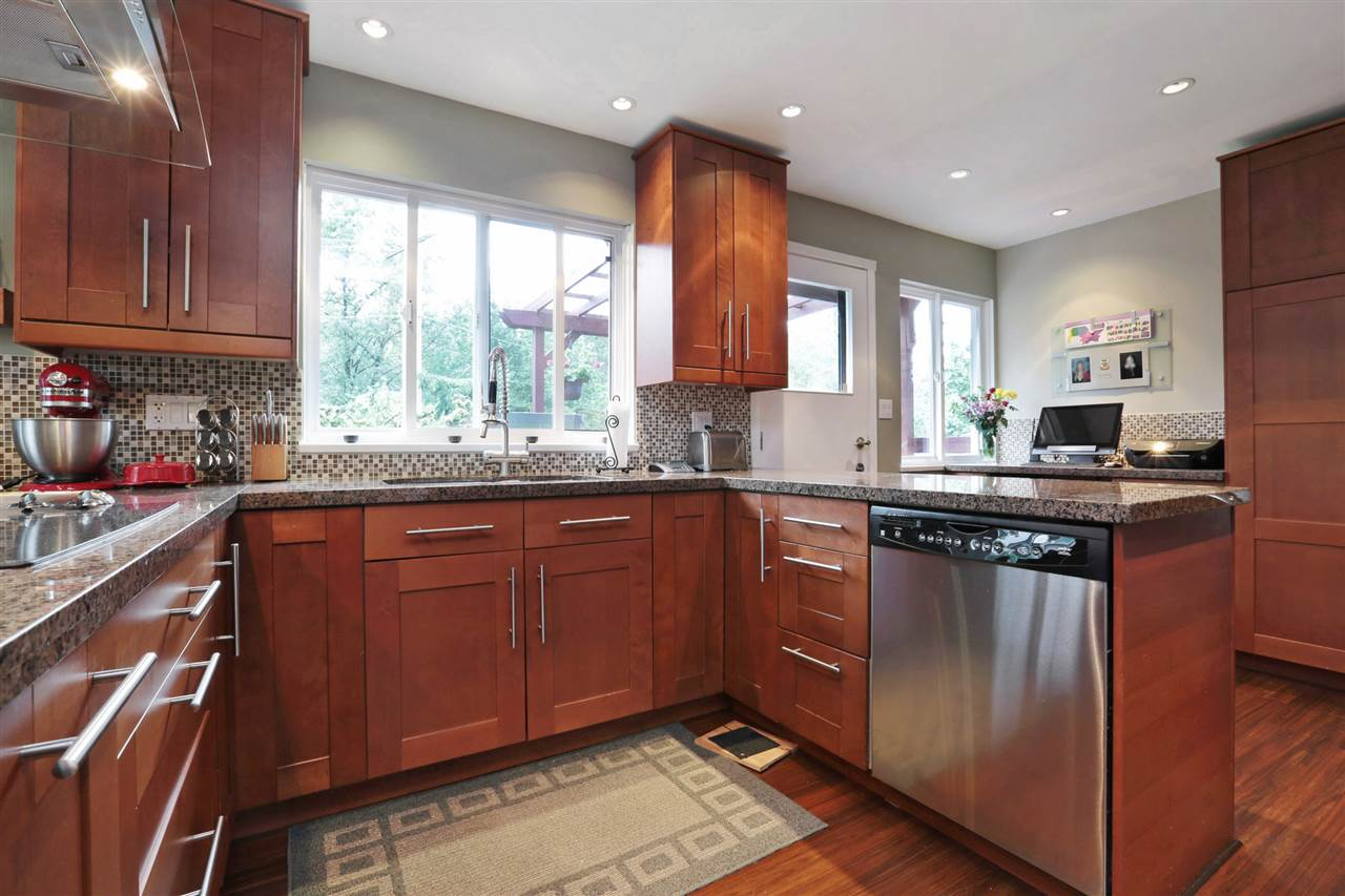 Cherry kitchen with stainless double ovens, electric cooktop, dishwasher, stacking washer & dryer