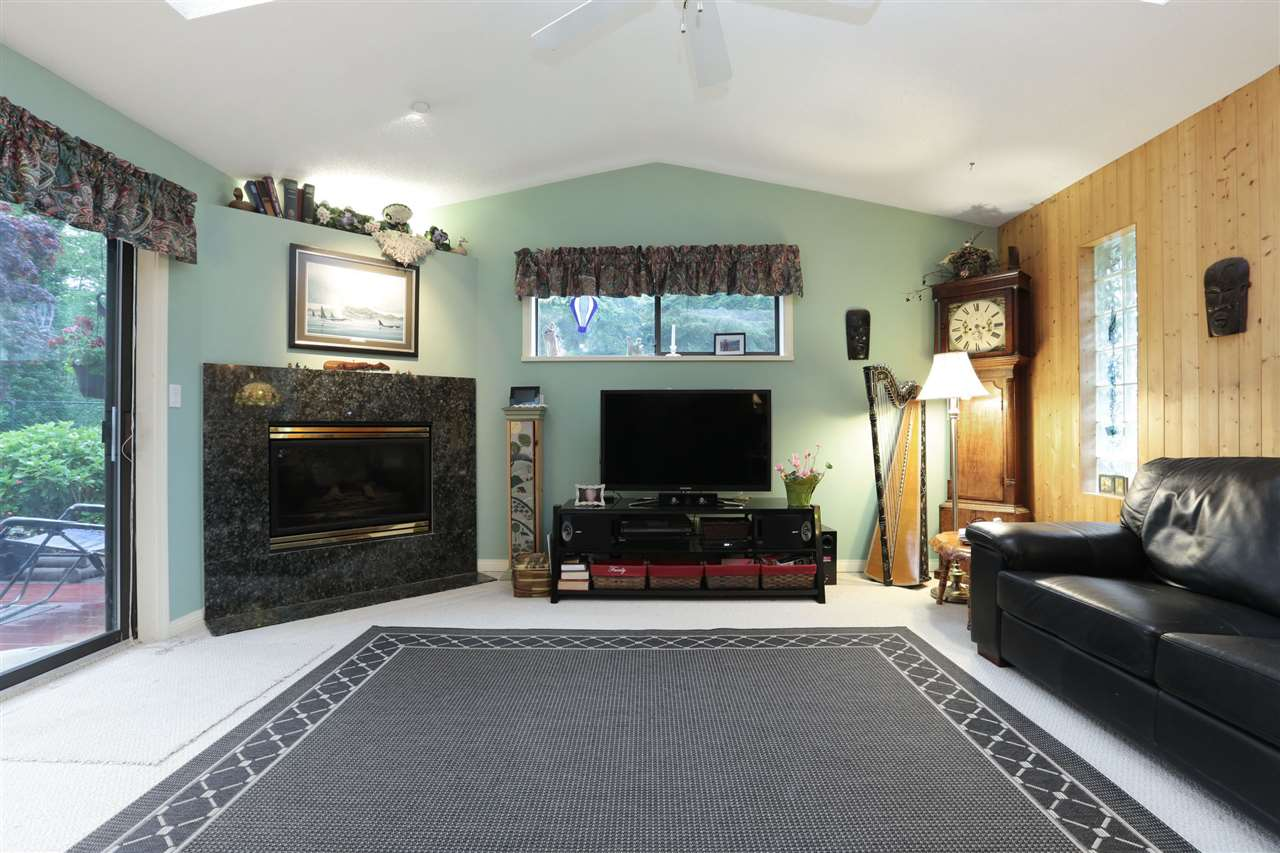 Down: Large bright living room with gas fireplace, skylight and level walk out to patio