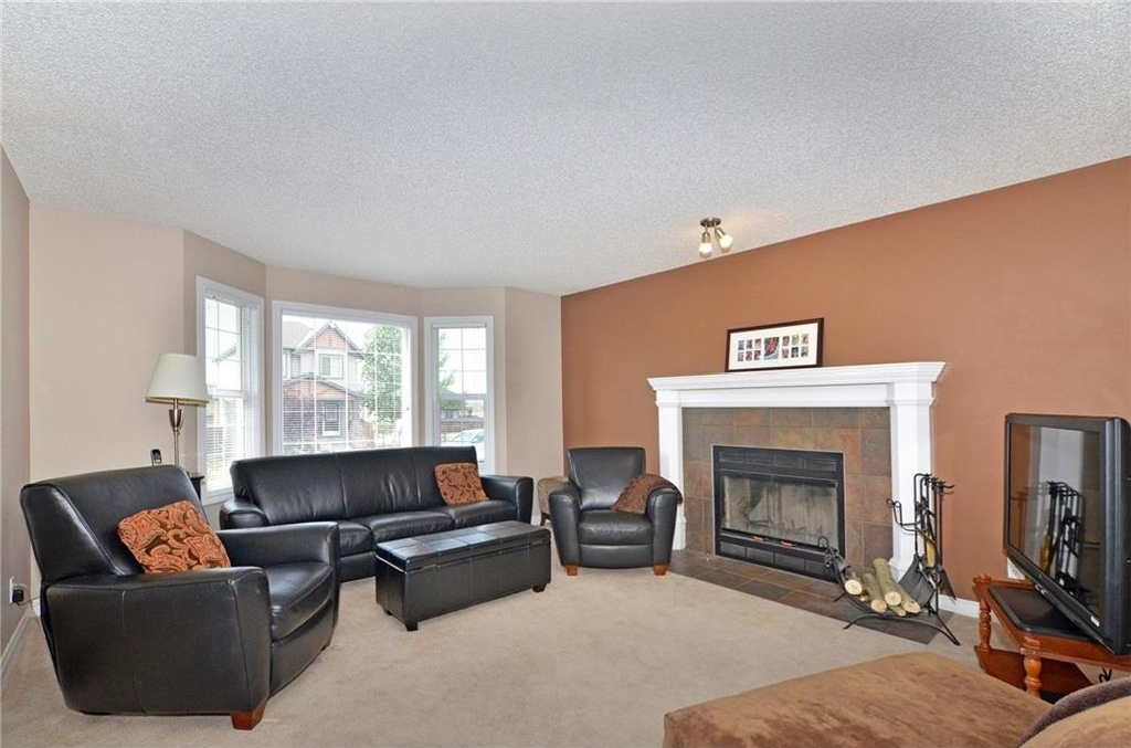 The bright living room greets you as you enter with a bay window and a wood burning fireplace with gas conversion