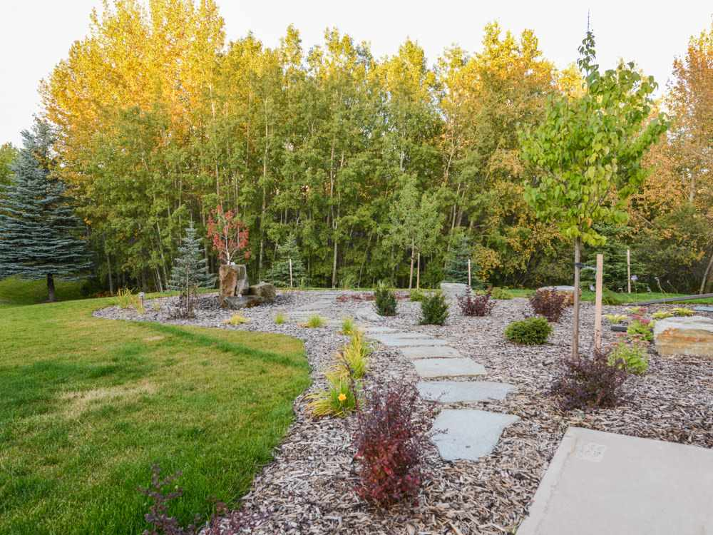 Extensive professional landscaping incl. large stream-like water feature with sitting area. Plenty of stone walking paths, trees and shrubs. Accent lighting for night. Irrigation system is run from the well on this property.