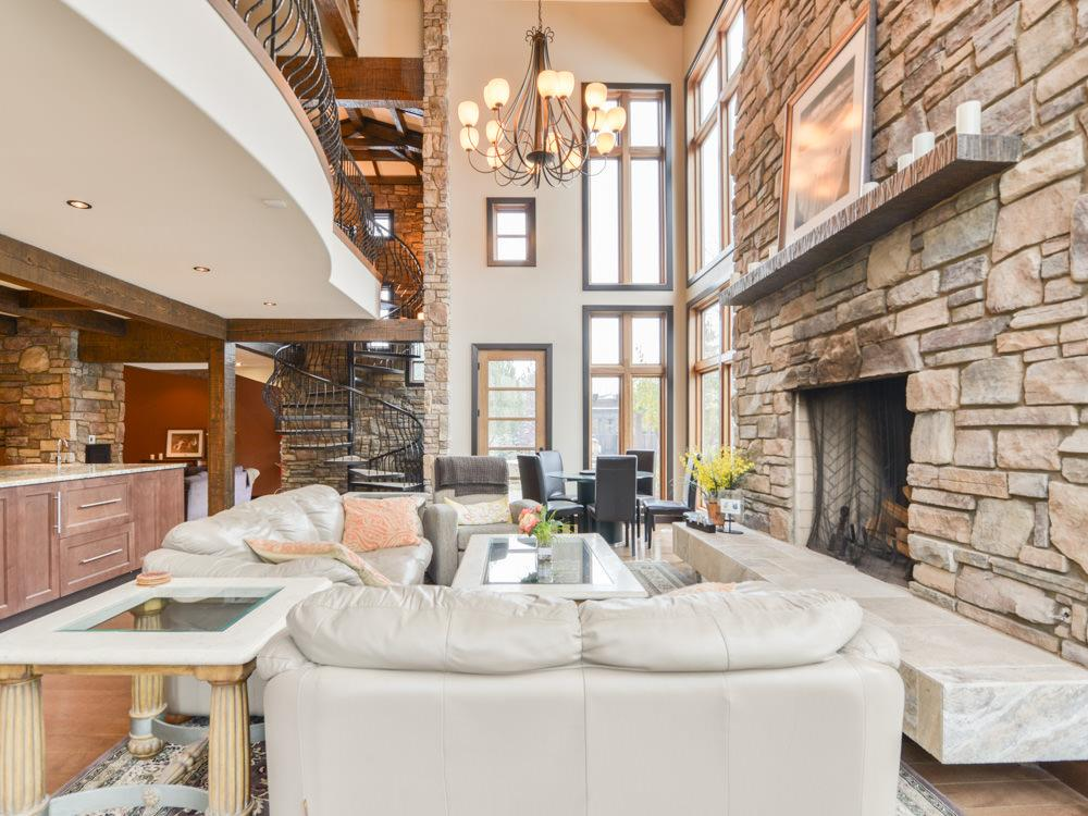 Very grande, this family room boasts a huge floor to ceiling stone, wood burning fireplace w/limestone hearth and is surrounded with floor to ceiling cascading windows.   Built-in cabinetry and granite counter.