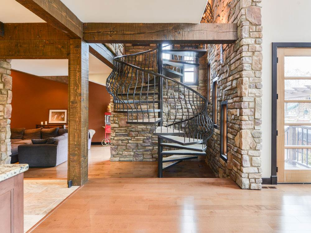 Custom designed, wrought iron, open riser spiral staircase with limestone steps is showcased within a feature stone wall.
