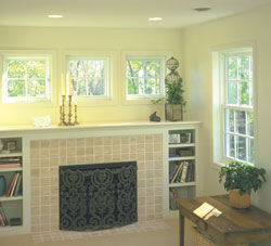 Three white awning windows over a fireplace & mantle. Up high, the replacement windows crank open for easy use.