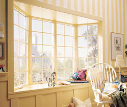 A bay replacement window with traditional maple interior and maple window seat expands a home