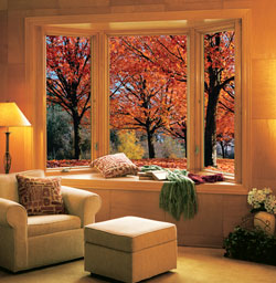 A bay window with pine wood veneer interior & glass without grids creates a stunning view of fall leaves.