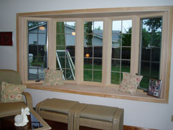 5 replacement windows combined to form a bow window overlook a garden. Wood maple interior and window seat.