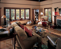 A bow replacement window with pine wood window seat and interior expands a living room in a home.