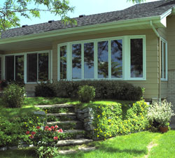 Replacement window combinations: Six casement windows in a curve form a bow window and overlook a garden.
