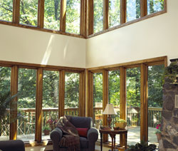 A two-floor suite of replacement picture windows with interior pine veneers forms a glass wall.