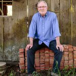 Winemaker and Ramey founder David Ramey seated on a pile of bricks in front of a weathered wooden outbuilding