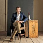 Portrait of Penfolds chief winemaker Peter Gago seated with bottle and wooden case