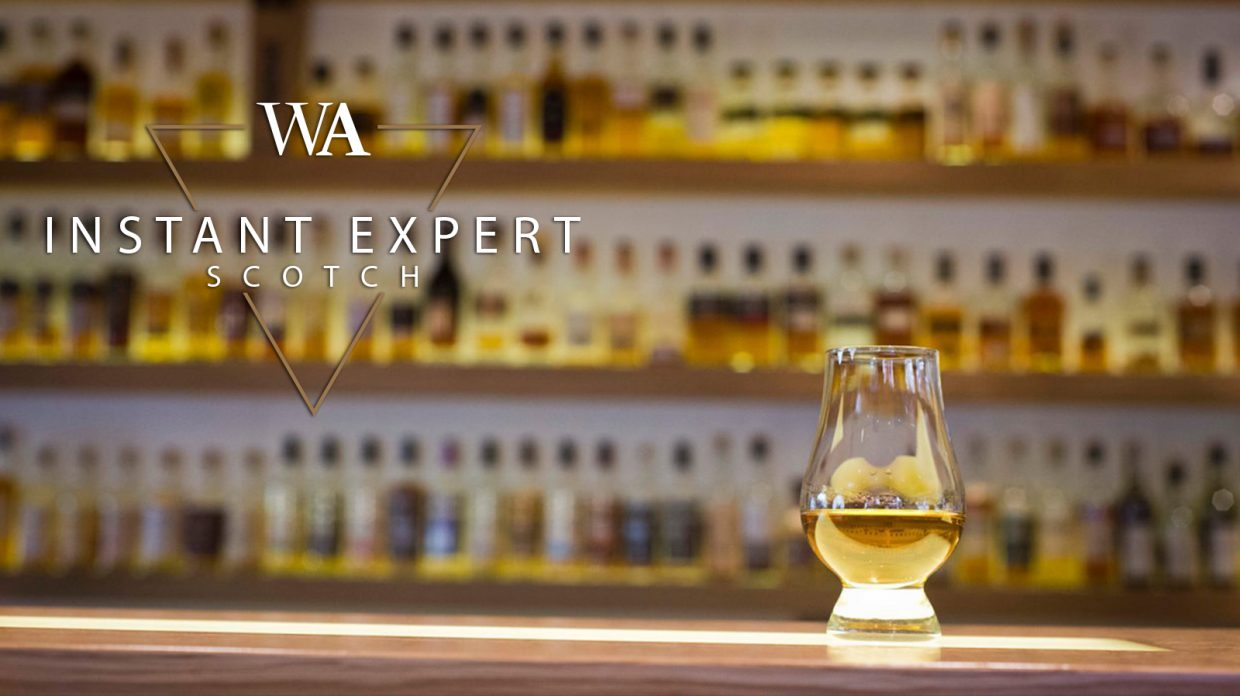 """Glencairn glass of scotch whisky in front of a shelf of bottles with the words """"Instant Expert Scotch"""" and Whisky Advocate logo."""