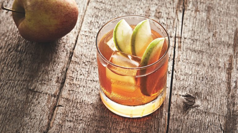 rocks glass with ice cubes and three apple slices in whiskey cocktail