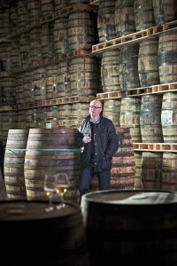Kevin O'Gorman, head of maturation at Irish Distillers Limited, leans against a large barrel, glass of whiskey in hand.