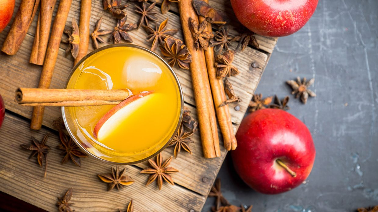 A cocktail garnished with a cinnamon stick and apple slice resembling the Brandied Rye and Apple Punch cocktail rests on a wooden board next to more apples and cinnamon sticks.
