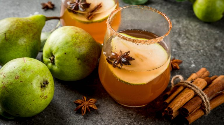 A cocktail garnished with a pear slice and spices, alongside a bundle of cinnamon sticks, pears, and star anise, resembling the Bucky Barnes cocktail rests upon a gray surface.