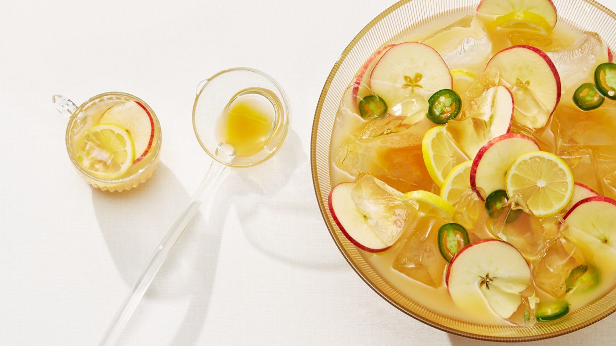 A bowl containing whisky punch including lemon, jalapeño, and apple slices rests on a white surface next to two glasses also containing punch.