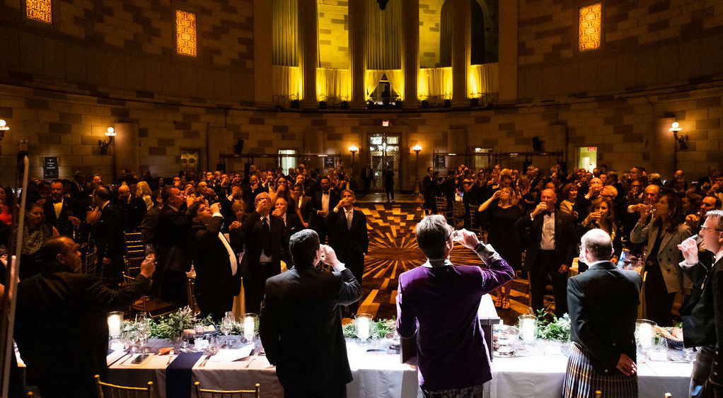 A large oval room full of dinner guests with a head table drinking a toast