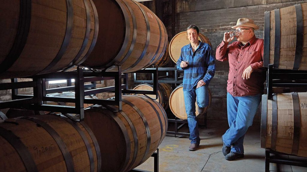 Pennsylvania farmer Nevada Mease wearing what appears to be a blue and black flannel shirt and blue jeans, leans against a whiskey barrel in a barrel warehouse, smiling, holding a glass of whiskey in his right hand. To his left stands Dad's Hat distiller Herman Mihalich wearing a red button-down shirt and blue jeans, also leaning against whiskey barrels, and sipping from a glass of whiskey.