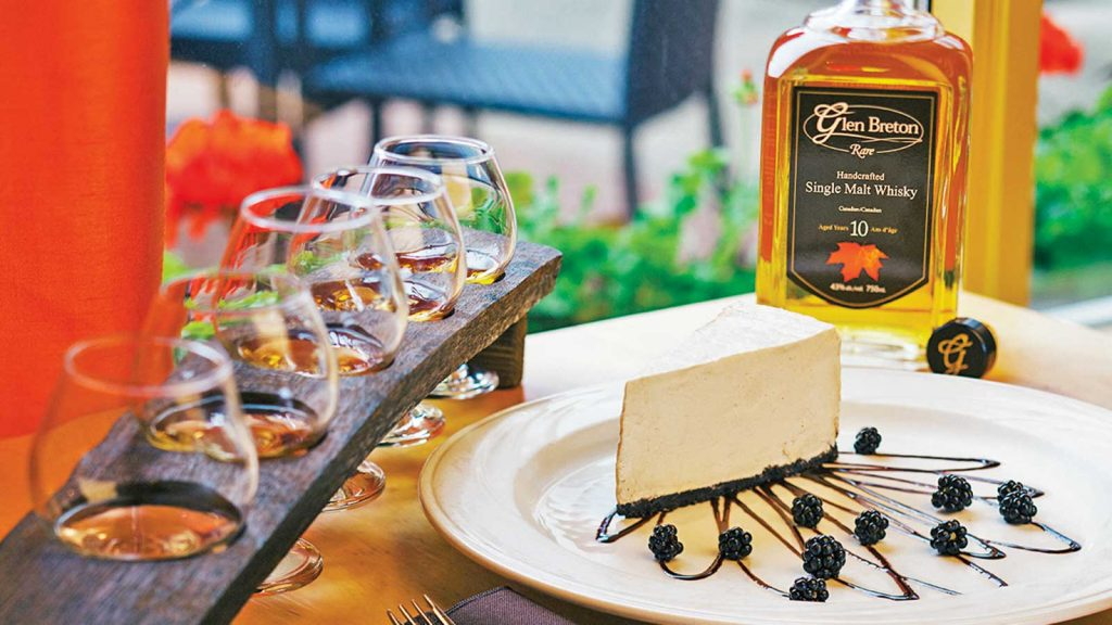 A flight of whiskies from Glenora Distillery in Nova Scotia, Canada rests on a table next to what appears to be a slice of cheesecake and a bottle of Glen Breton Rare 10 year old single malt.