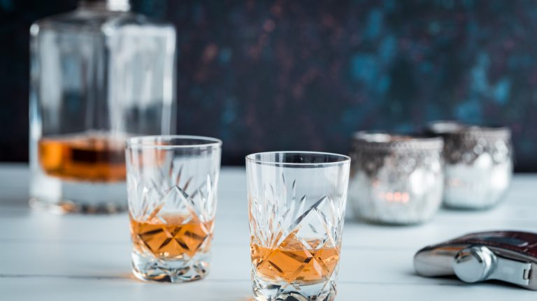 Close up color image depicting two fine crystal glasses of malt whisky on a white wooden surface. The glasses of whisky are surrounded by whisky paraphernalia such as a glass decanter and a hip flask