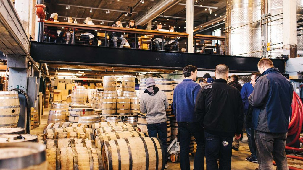 Visitors to Journeyman Distillery in Three Oaks, Michigan stand among whiskey barrels.