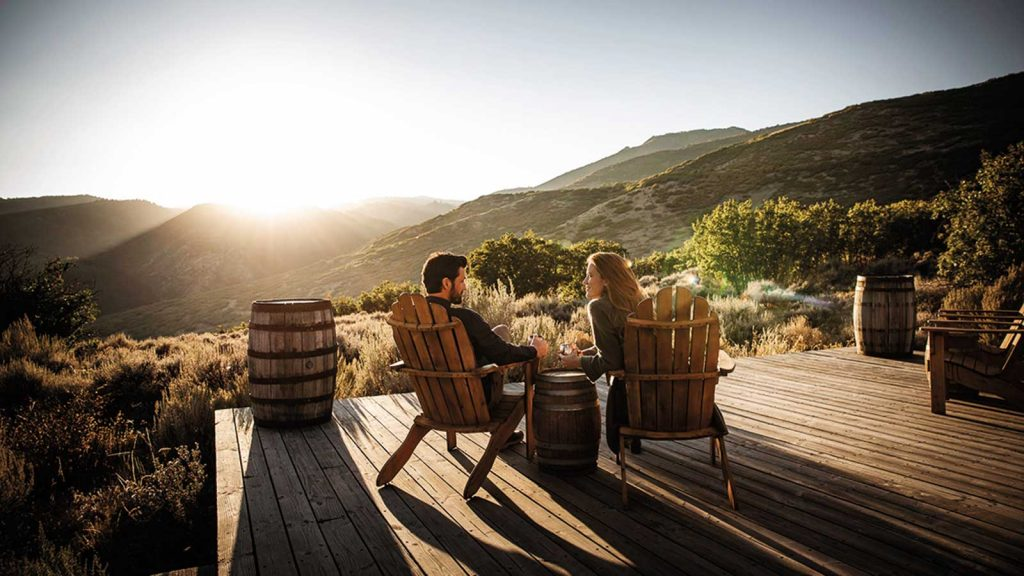 A man and a woman relax in wooden chairs overlooking what appears to be the sun setting behind a breathtaking mountainous landscape in Wanship, Utah.