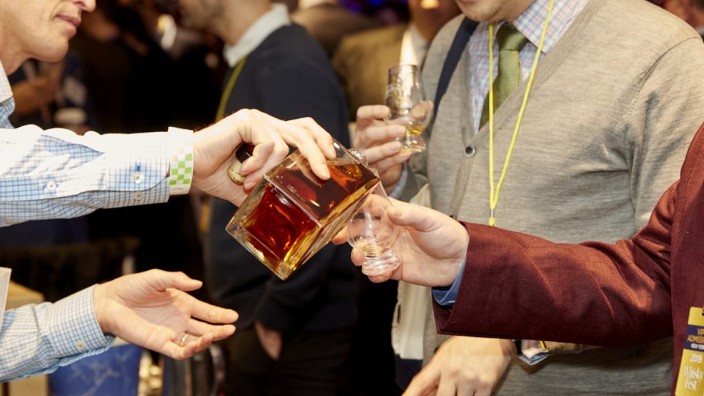 An exhibitor at WhiskyFest New York 2019 pours from a bottle of whisky into a Glencairn held by a whisky taster.