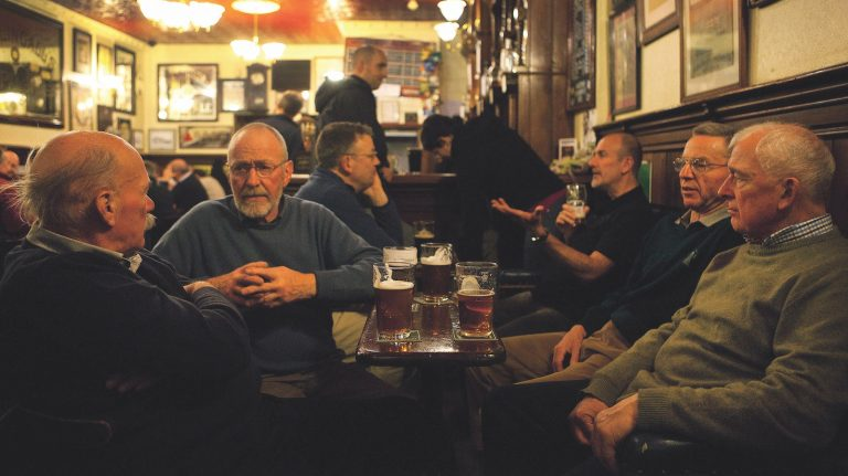 Several men gather to drink beer at the Bow Bar in Edinburgh, Scotland.