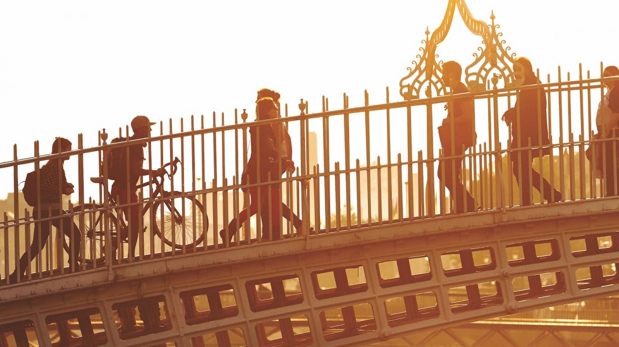 Six people stroll over Dublin's Ha'Penny Bridge, all in silhouette as the sun is setting behind them.