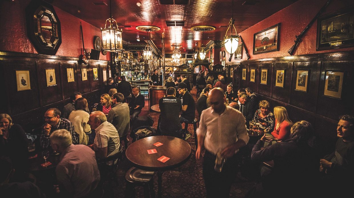 The interior of The Long Hall, a Dublin pub, which is full of people on all sides and at all tables.