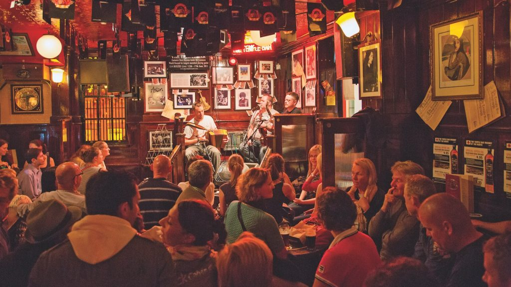 Several guests are seated at tables with food and drink, listening to a band of three men playing folk music in Dublin's dimly lit Temple Bar.