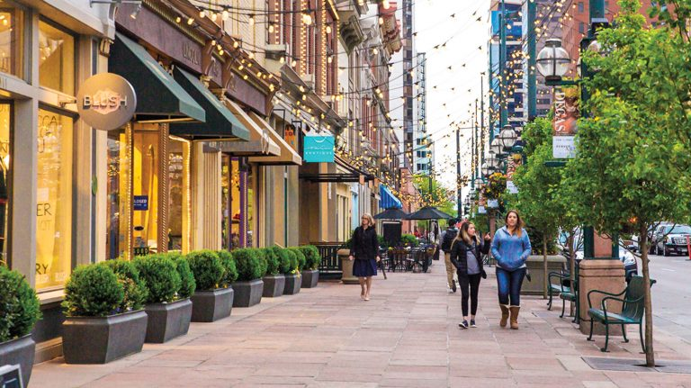 Pedestrians walk in the daylight, under what look like overcast skies, along a commercial street in Denver under hanging small lights, next to trees and benches, in front of what appear to be shops and businesses.