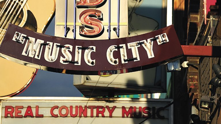 "Signs for various music venues in Nashville, Tennessee grace the sidewalks, including one, in view, that says ""Music City."""