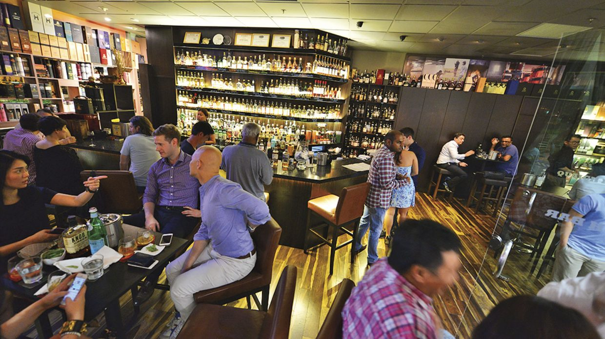 Patrons sit and stand at tables and at the bar enjoying whisky, other beverages, and snacks at Quaich Bar, Singapore's first whisky bar, which whisky wholesaler-retailer The Whisky Store opened in 2007; in the background, bottles line shelves behind the bar, as well as along the walls.