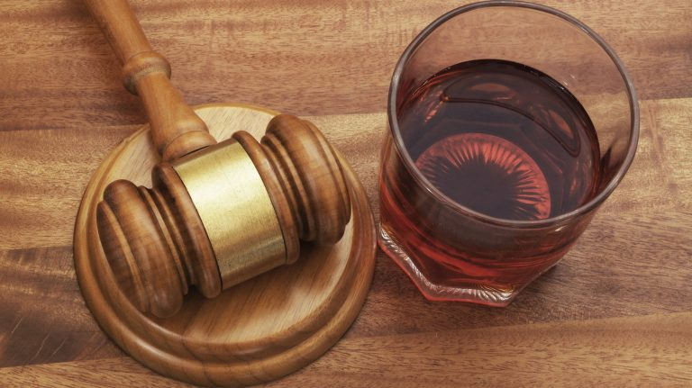 A glass of brown liquid sits next to a gavel on a wooden table.