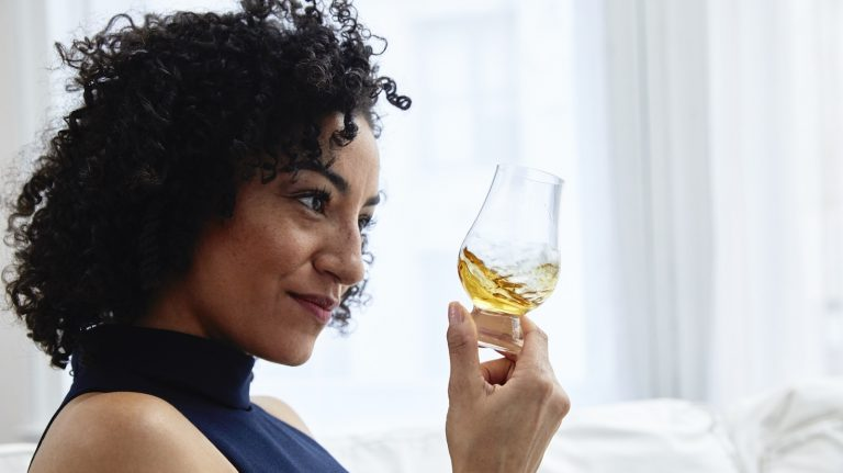 A woman swirls a Glencairn glass that is partially full of whisky.